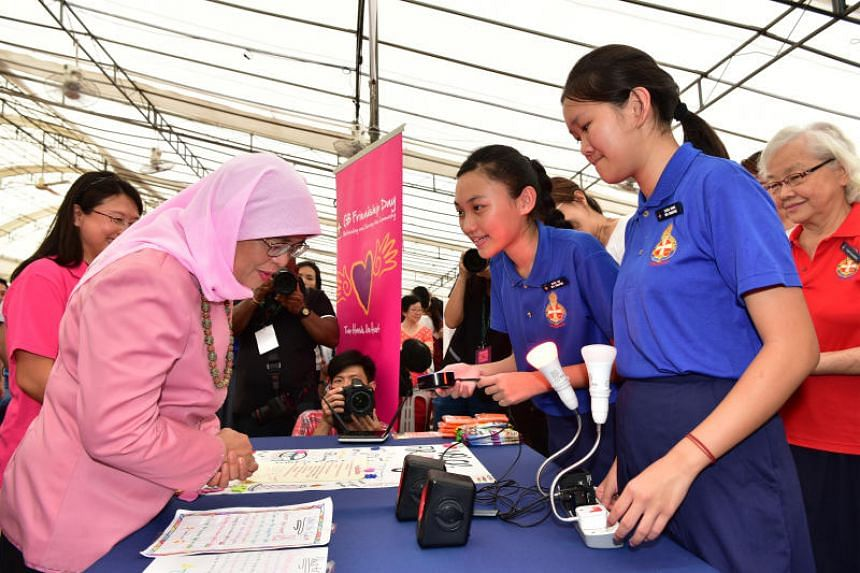 Girls Brigade Singapore members demonstrating how to use a voice-enabled device programmed by them to President Halimah Yacob at the Girls Brigade Friendship Day 2018 on July 14, 2018.