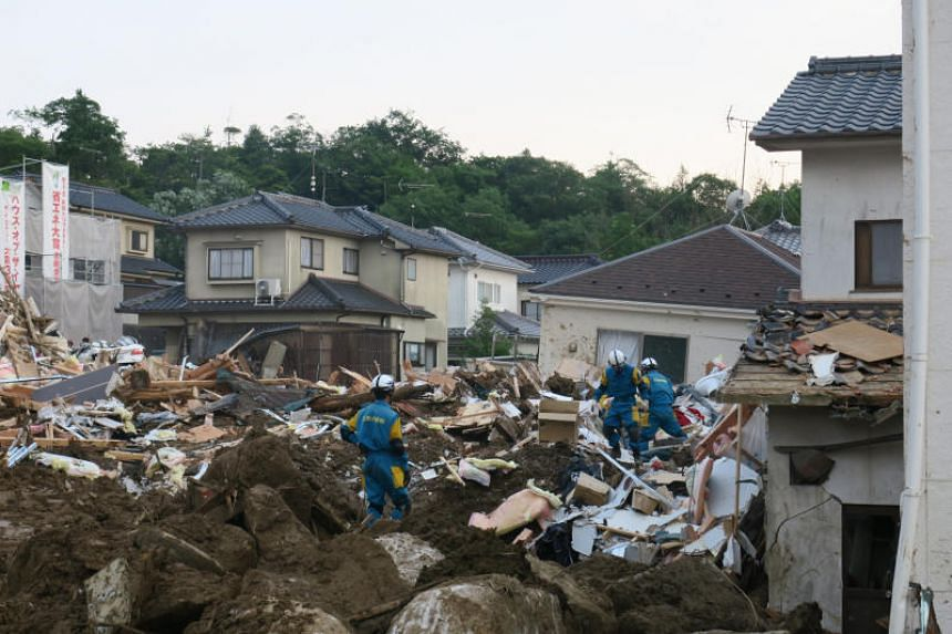 """Police officers work through the debris after the landslide at """"Ohara Heights"""" in Kawasumi 5-Chome, Kumano district, Hiroshima prefecture, on July 12, 2018."""