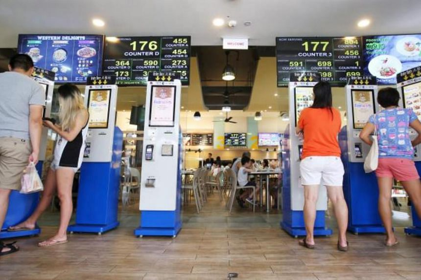 Patrons ordering food from kiosks at the entrance of the FoodTastic coffee shop in Choa Chu Kang Avenue 1.