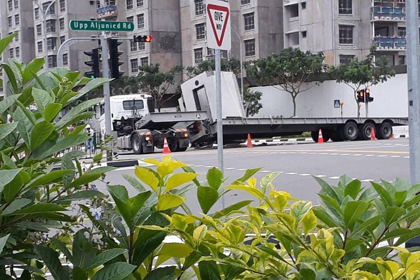 A precast concrete component, which appears to have fallen off the trailer, can be seen lying on the road.