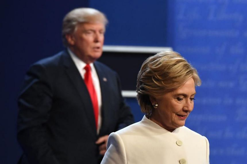 Former Democratic nominee Hillary Clinton (right) and former Republican nominee Donald Trump walking off the stage after the final presidential debate at the Thomas & Mack Center on Oct 19, 2016.