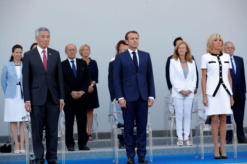 Prime Minister Lee Hsien Loong, French President Emmanuel Macron and his wife Brigitte Macron attend the annual Bastille Day military parade on the Champs-Elysees avenue in Paris, on July 14, 2018.