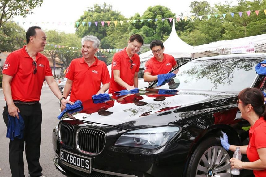 Great Eastern's Group CEO Khor Hock Seng (second from left), together with top management, staff and agent volunteers, washing cars for the Straits Times School Pocket Money Fund.