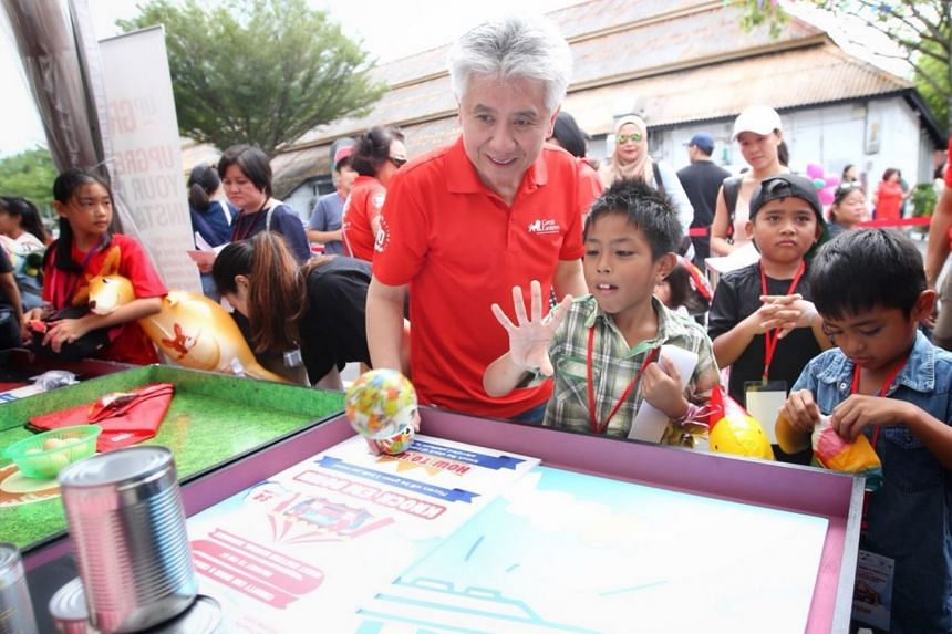 Great Eastern's Group CEO Khor Hock Seng and children beneficiaries of The Straits Times School Pocket Money Fund playing a game at a stall.