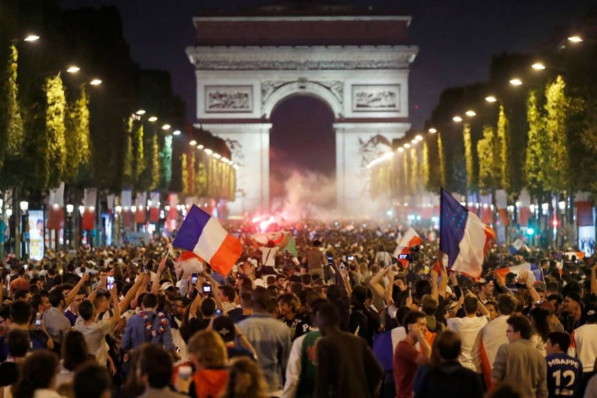 Football fans celebrating on the Champs-Elysees after France defeated Belgium in the semi-finals of the World Cup, on July 10, 2018.