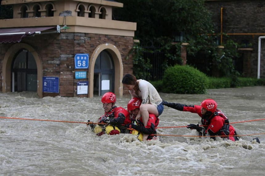 Firefighters rescuing a stranded woman on a flooded street, following heavy rainfall in Chengdu, Sichuan province, China, on July 11, 2018.