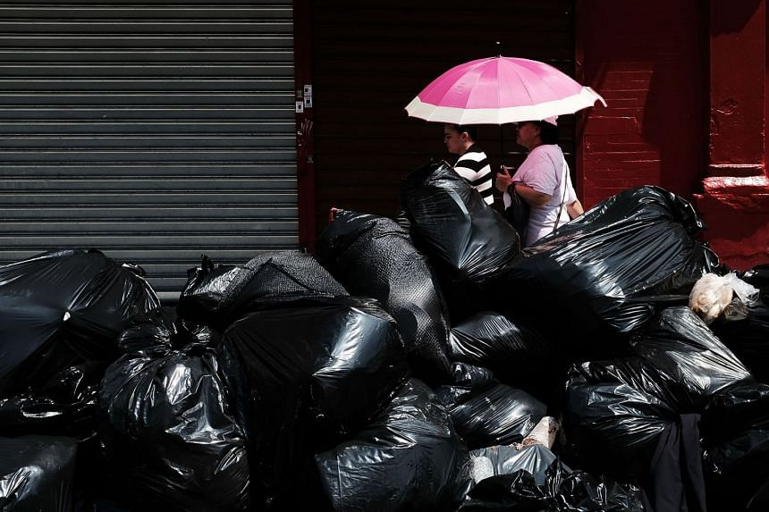 Pedestrians walking by piles of trash in the Bronx, one of the poorest congressional districts in the nation in New York City, on July 11, 2018.