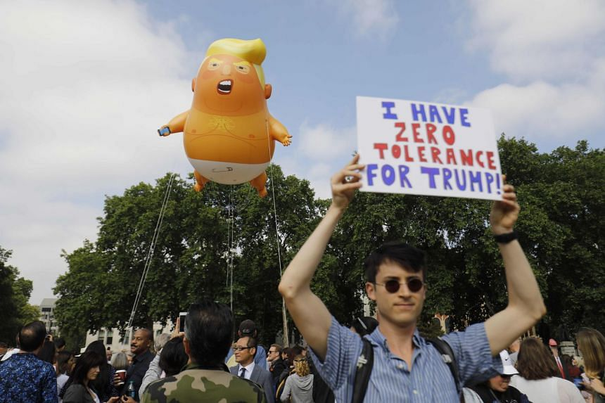 Protesters gathering around a giant balloon depicting US President Donald Trump as an orange baby during a demonstration against his visit to Britain at Parliament Square in London yesterday.