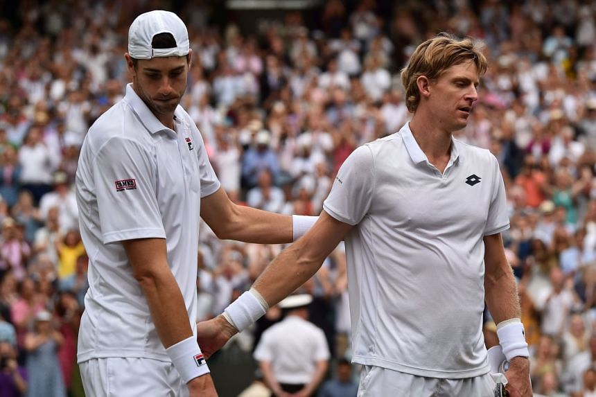 Anderson (right) shakes hands with Isner after winning the final set tie-break.
