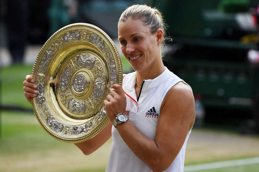Kerber celebrates winning the women's singles final with the trophy .