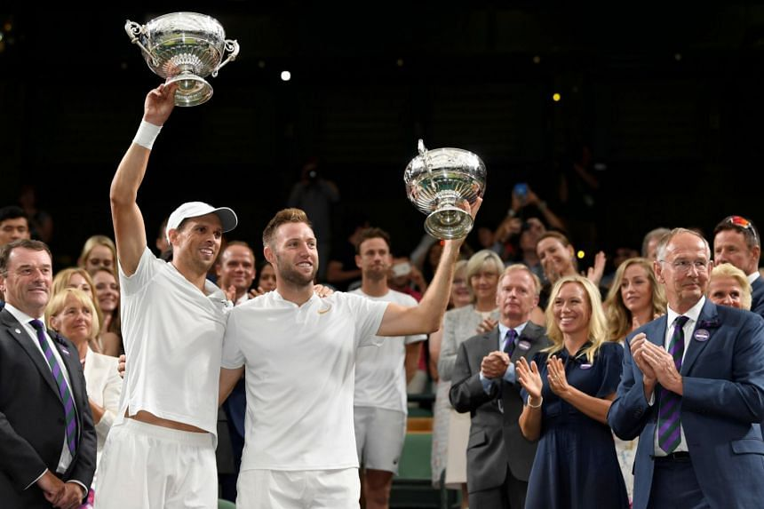 Jack Sock and Mike Bryan of the US celebrate with the trophies.