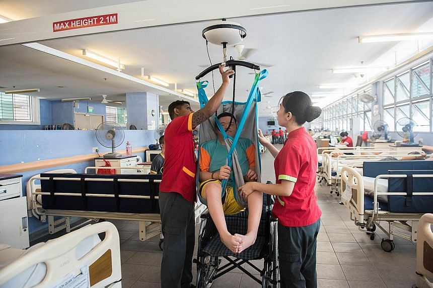 Healthcare aide Nalawayaa Suranga (left) and nursing aide Glaiza Minasalvas hoisting up Mr Goh Quan Yao at the Red Cross Home for the Disabled to transfer him from the bed to the wheelchair. The aides no longer need to strain to lift bed-bound patien