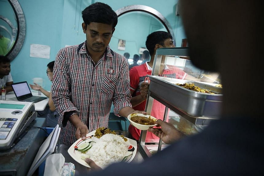 Injured Bangladeshi worker Motin Abdul, 29, collecting his meal at Isthana Restaurant. He stopped working when he suffered back and elbow injuries, as well as hearing loss, after a worksite accident in May.