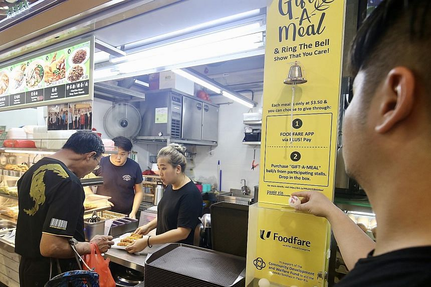 """Diners can donate a meal by buying """"Gift-A-Meal"""" balls from stalls in Pasir Ris Central Hawker Centre and dropping them in a box."""
