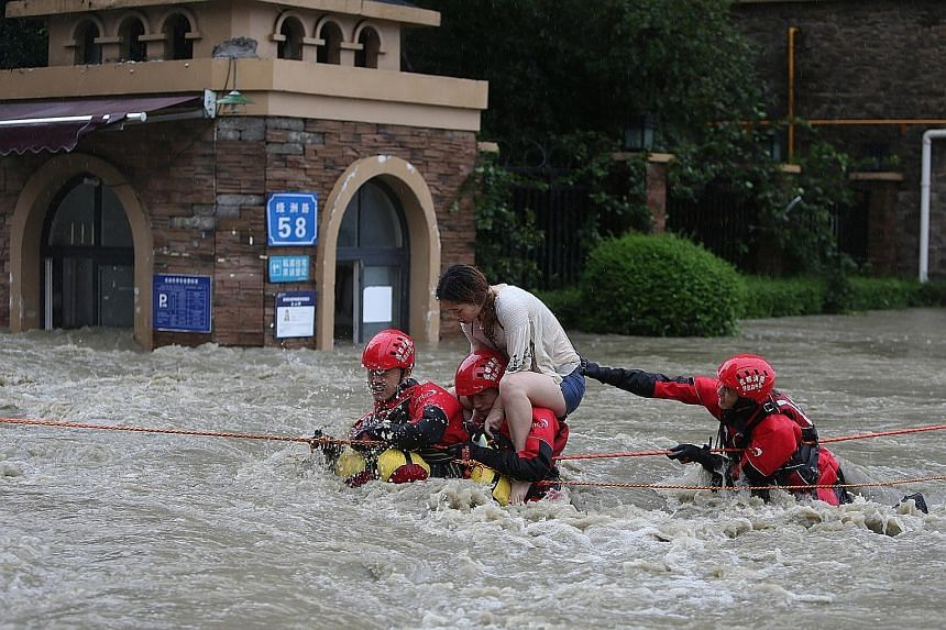 Right: A flooded village in Zoige county, in the south-western province of Sichuan, on Friday. Far right: Firefighters rescuing a stranded woman, following heavy rainfall in Chengdu, in Sichuan province. Left: A landslide hit a township in Zhouqu cou
