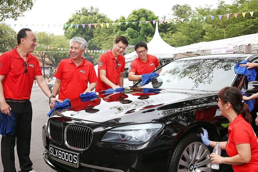 Great Eastern group chief executive Khor Hock Seng (second from left) was among 170 staff from the company who rolled up their sleeves to wash cars yesterday - all in the name of charity. They raised more than $60,000 for The Straits Times School Poc