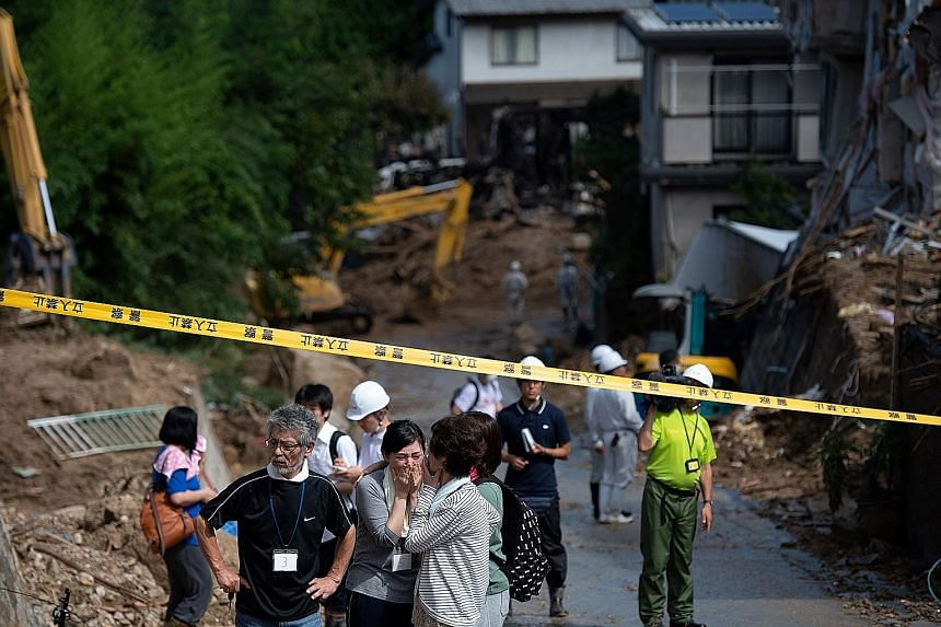 Top: A soldier collecting photos from debris at a landslide site in Kumano Town. Above: Muscat grapes that Mrs Kaori Kataoka's father grew were damaged. Above: Refrigerators damaged by flooding are seen at a temporary waste-collection point at Mabi C