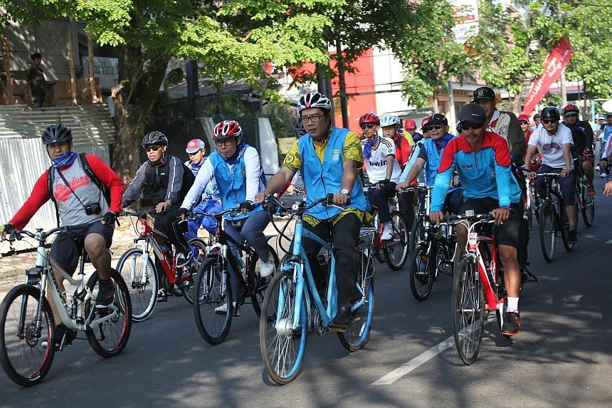 Mr Ridwan (centre) cycling in Bandung in 2014 during the launch of a campaign to promote commuting by bicycle. A 2012 photo of Mr Ridwan, an architect and recycling advocate, who used 30,000 Red Bull bottles in the design of his Bandung house. Mr Rid