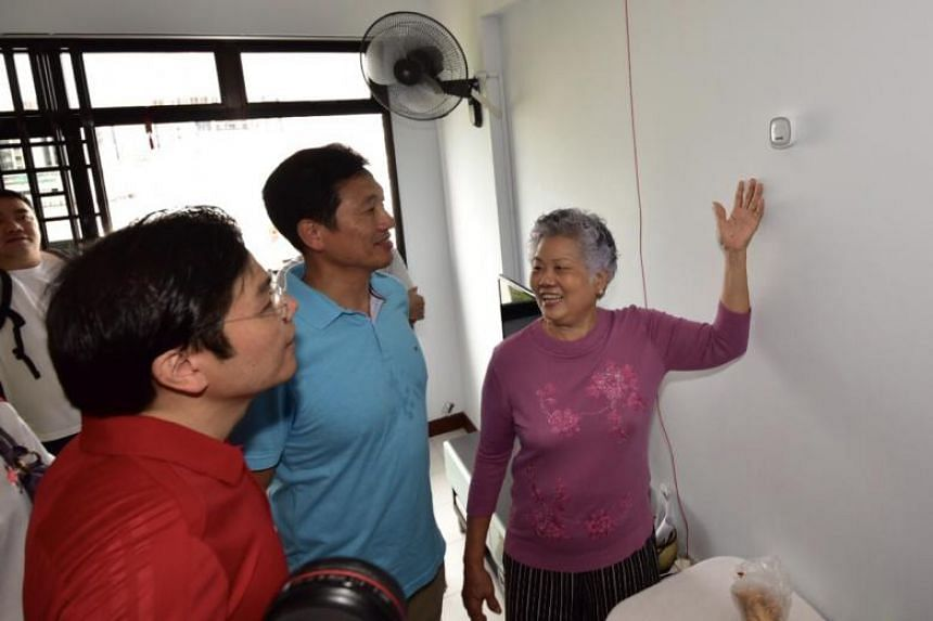 From left: National Development Minister Lawrence Wong and Education Minister Ong Ye Kung with Madam Teng Ah Moi, who was showing the safety features in her flat, during a ministerial community visit to Jurong Central, on July 15, 2018.