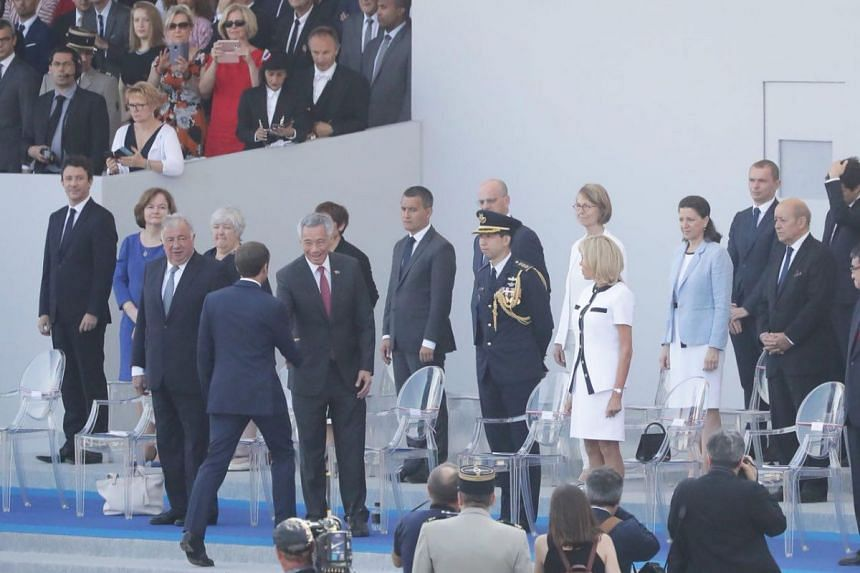 French President Emmanuel Macron welcomes Prime Minister Lee Hsien Loong at Bastille Day celebrations on the Champs-Elysees Avenue in Paris on July 14, 2018.