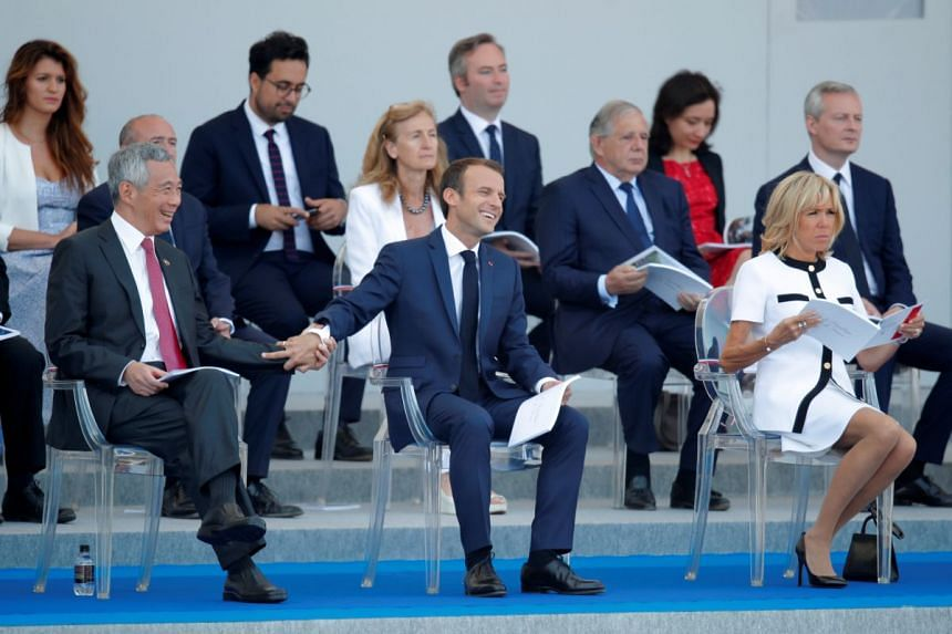Prime Minister Lee Hsien Loong, French President Emmanuel Macron and his wife Brigitte Macron attend Bastille Day celebrations on the Champs-Elysees in Paris on July 14, 2018.