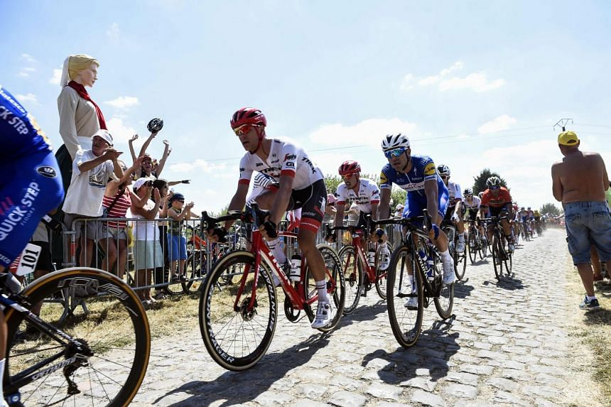 Spectators cheering riders pedalling through the ninth stage's first cobblestone section in Thun-l'Eveque in the 105th edition of the Tour de France cycling race between Arras and Roubaix, northern France, on July 15, 2018.