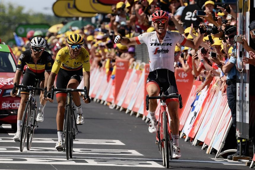Germany's John Degenkolb celebrating as he crosses the finish line ahead of Belgium's Greg Van Avermaet (yellow jersey) and Belgium's Yves Lampaert to win the ninth stage of the Tour de France on July 15, 2018.