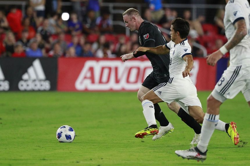 DC United's Wayne Rooney and Vancouver Whitecaps' Nicolas Mezquida fighting for the ball during their MLS match on July 14, 2018.