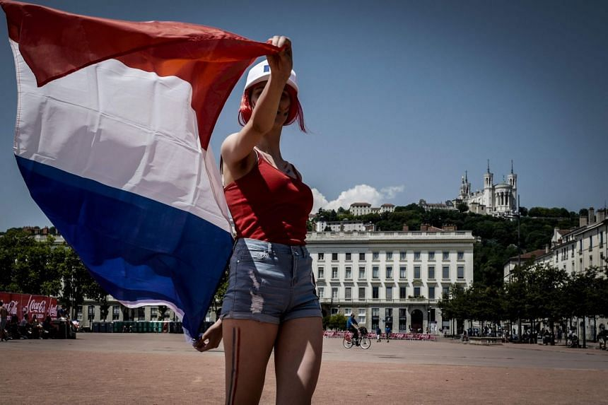 A French fan holding up the national flag in Lyon ahead of the national team's World Cup final match against Croatia, on July 15, 2018.