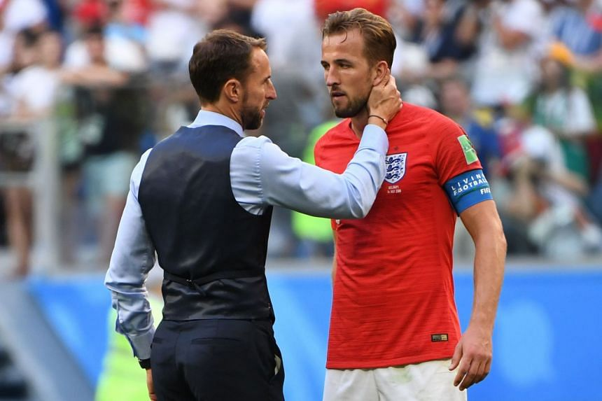 England's coach Gareth Southgate talks to forward Harry Kane after losing the match.