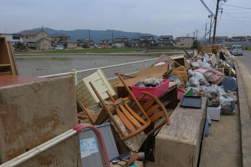 The roads of Mabi district in Kurashiki, Japan, are lined with water-damaged furniture, and garbage bags full of mud-soaked clothing, books and utensils that residents have thrown out.