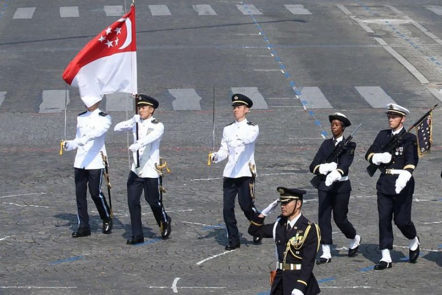 Singapore's Flag Party, led by Contingent Commander Major Nicholas Tong Jun, carrying the Republic's flag at the parade. Left: A combined flypast involving an RSAF M-346 Advanced Jet Trainer and five French Air Force Alpha Jets.