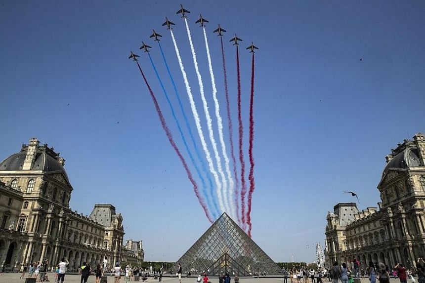 The Patrouille de France military aircraft passing over the Louvre Museum's pyramid during the traditional Bastille Day military parade. The event featured about 4,000 soldiers, 220 vehicles, 250 horses, 64 aircraft and 30 helicopters. Among these we