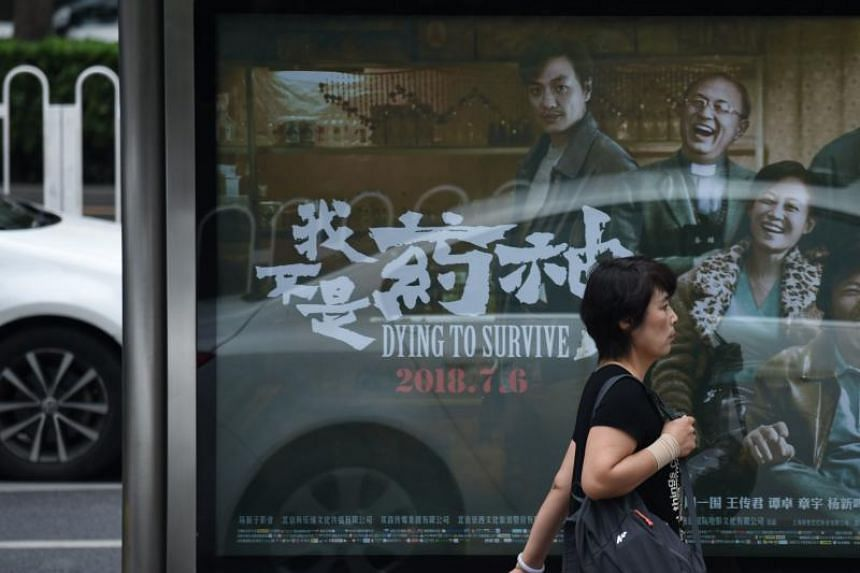 A woman walks past a poster for Dying To Survive, a film about a cancer sufferer who illegally imports foreign medicine to China, in Beijing on July 12, 2018.