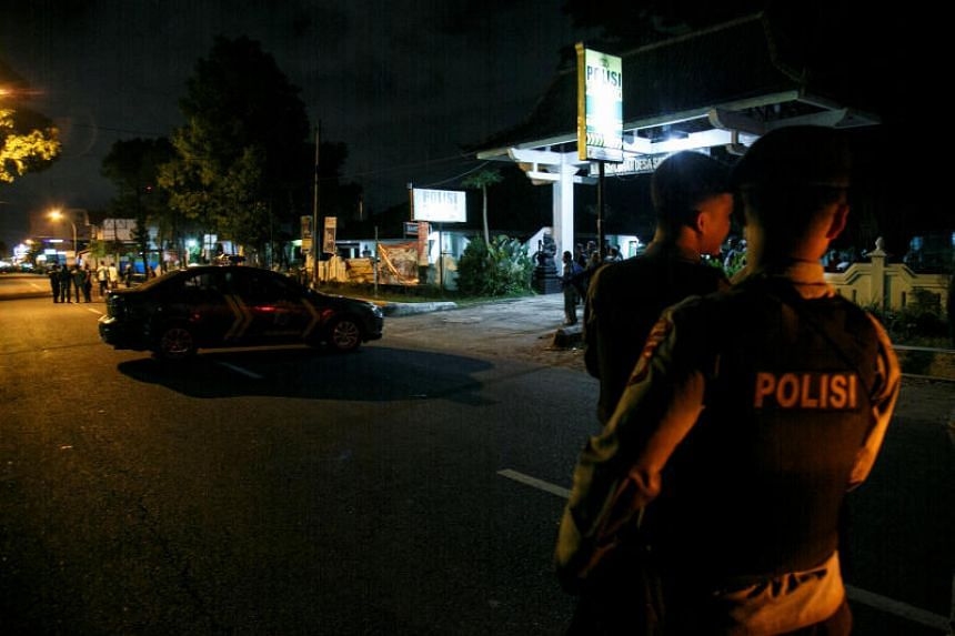 Indonesian police officers are seen standing guard near the scene of a shooting in Sleman, Yogyakarta, on July 14, 2018.