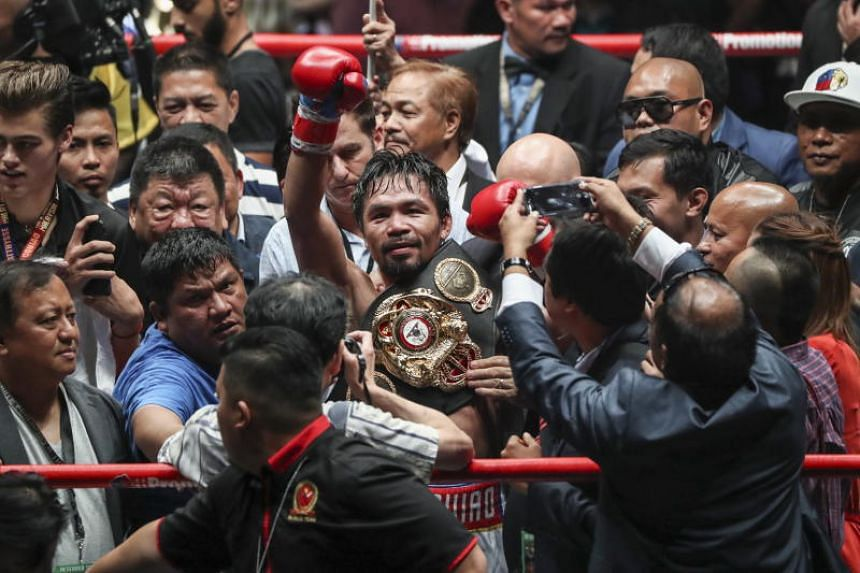 Filipino boxing icon Manny Pacquiao (centre) celebrates after defeating Argentina's Lucas Matthysse during their WBA welterweight championship fight, dubbed 'Fight of the Champions' in Kuala Lumpur, Malaysia, on July 15, 2018.