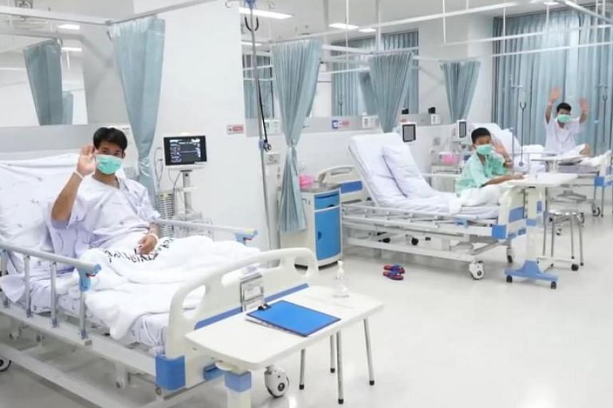 "Members of the ""Wild Boars"" football team, together with coach Ekkapol Chantawong (left) waving to visitors while recuperating in the hospital, on July 14, 2018."