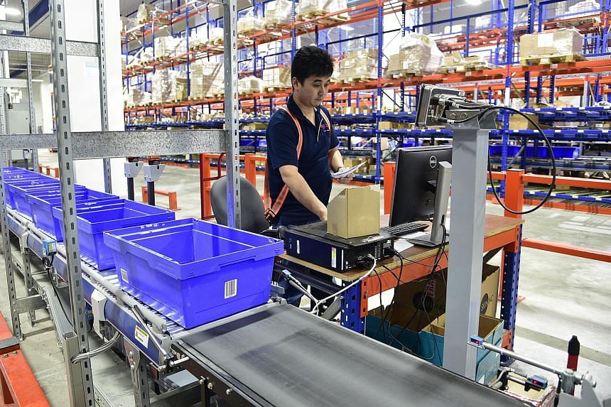Couriers from SP Parcels check a parcel before it is placed in a delivery van. Speedpost is a last mile door-to-door express delivery service by SP Parcels, a subsidiary of SingPost. Couriers loading parcels containing customers' orders onto delivery