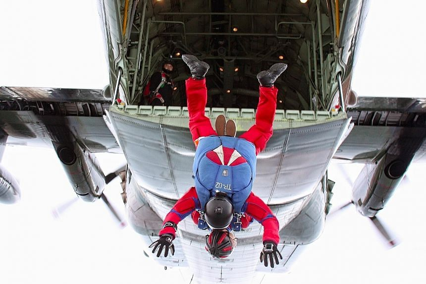 Here we go! ST photojournalist Mark Cheong and Red Lions First Warrant Officer Dave Chong moments after the jump in their tandem sky dive last Monday. The Red Lions' cameraman, Major Arnold Low, gesturing to Mr Cheong to smile for the camera. When th
