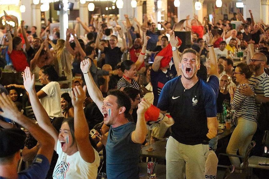 Guests at The Straits Times' viewing party cheering at 1-Altitude bar in Raffles Place, where 60 lucky subscribers and their plus ones joined ST staff and partners to catch the final. Croatia fans watch with their hearts sinking in Boat Quay. Ship ca