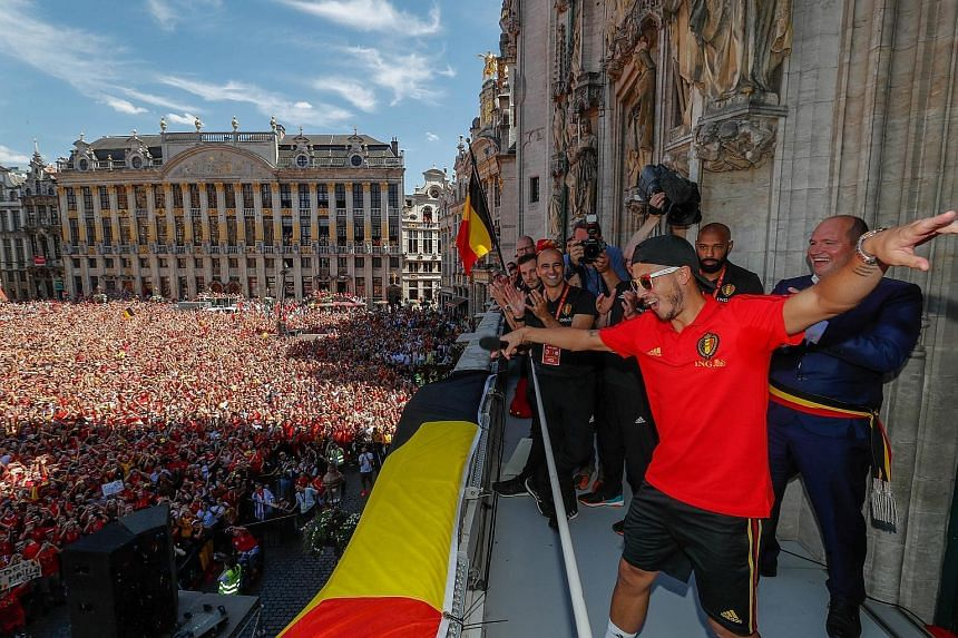 Belgium captain Eden Hazard strutting on the balcony of the Grand Place Town Hall in Brussels, to the delight of a jubilant crowd welcoming the team after they finished third in Russia.