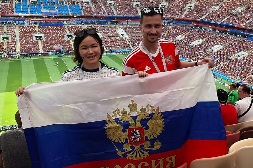 DMITRY PISMENNY and wife Michelle Cheong-Gautrin at the Luzhniki Stadium for the Russia-Spain last-16 game