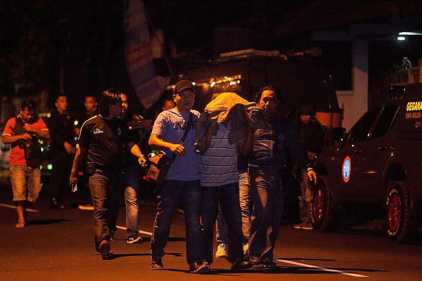 Above: Police officers with a suspect after three militants were killed in Yogyakarta on Saturday. Police had been tailing the trio and a fourth man when two of them attacked an officer. The three were shot dead and the fourth escaped. Left: Police o