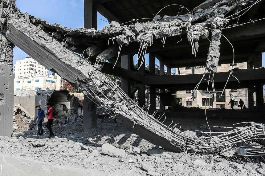 Young Palestinians walking through the wreckage of a building, damaged by Israeli air strikes in Gaza City, yesterday. Israel's military said the strikes targeted Hamas military facilities in the Gaza Strip, killing two Palestinians, while some 200 r