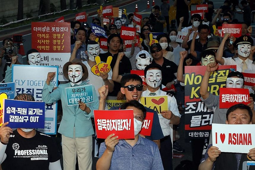 Employees of Korean Air and Asiana Airlines protesting outside the presidential Blue House in Seoul last Saturday. Korean Air chairman Cho Yang-ho is under probe for tax evasion and embezzlement, while Asiana Airlines employees have spoken out agains