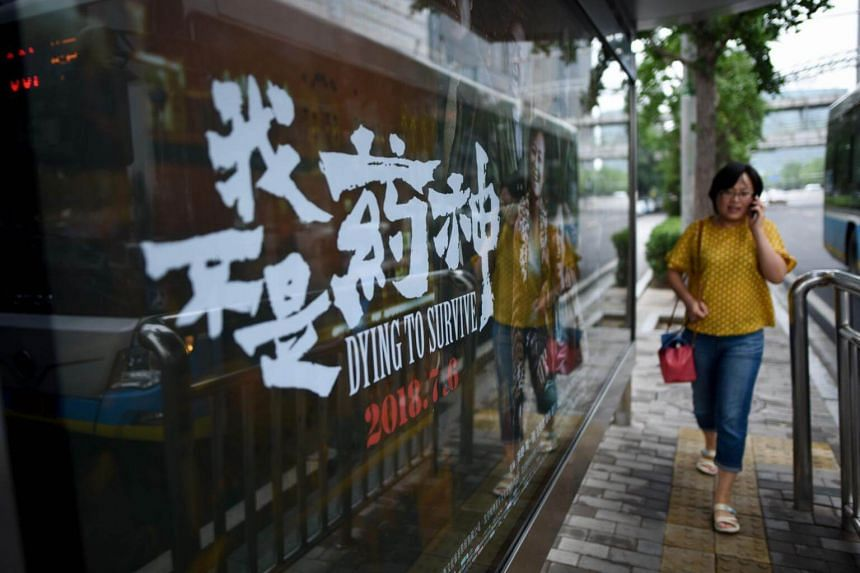 A woman walks past a poster of Dying to Survive, which is en route to becoming one of China's highest-grossing films.