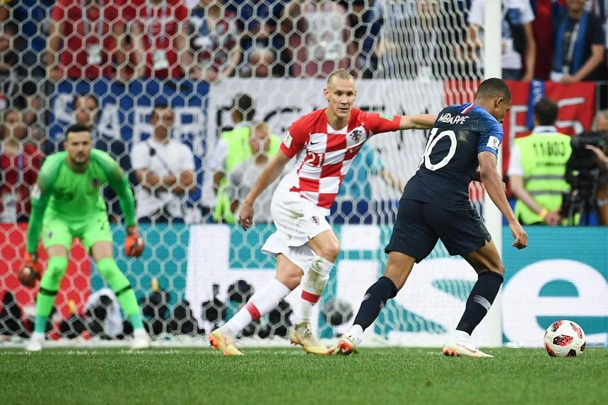 France's forward Kylian Mbappe (right) prepares to shoot and score his team's fourth goal during their Russia 2018 World Cup final football match between France and Croatia at the Luzhniki Stadium in Moscow on July 15, 2018.