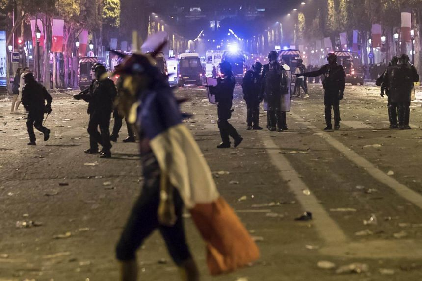French riot police dispersing people away on Champs-Elysees avenue after French supporters celebrated the victory of France at the FIFA World Cup 2018 final match against Croatia in Paris, France, on July 15, 2018.
