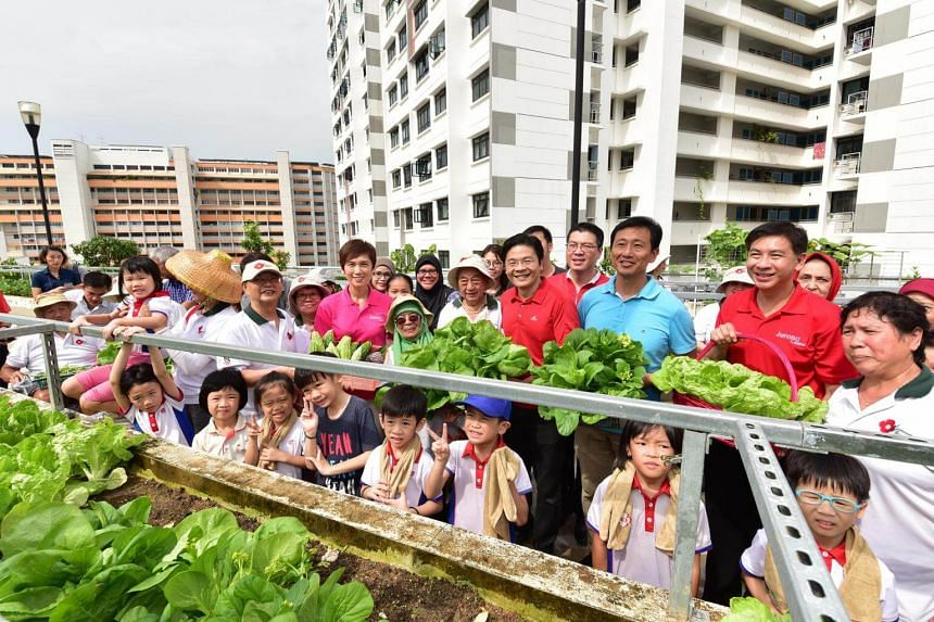 Education Minister Ong Ye Kung (third from right), National Development Minister Lawrence Wong (fourth from right) and Manpower Minister Josephine Teo (in pink) with Jurong GRC MP Ang Wei Neng (second from right), residents and kindergarten pupils at