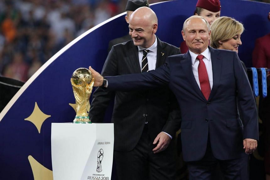 Russian president Vladimir Putin (right) touches the World Cup trophy as Fifa president Gianni Infantino smiles during the award ceremony in Moscow, Russia, on July 15, 2018.
